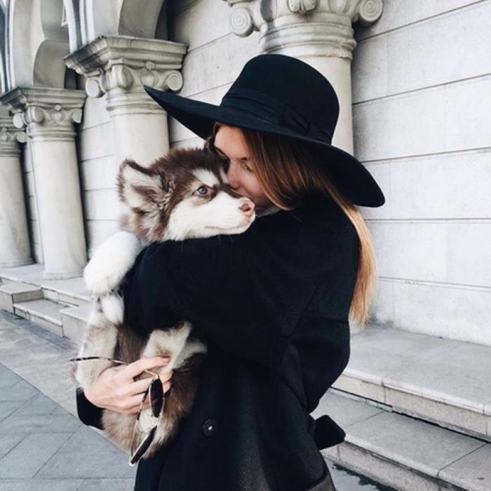 mujer de cabello castaño con sombrero negro abrazando a perro