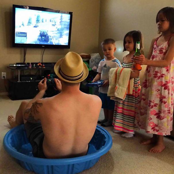 padre jugando en tina con hijos a un lado