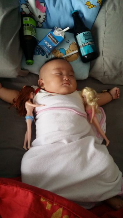 bebé rodeado de botellas y muñecas