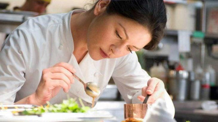 mujer de cabello negro cocina y decora plato