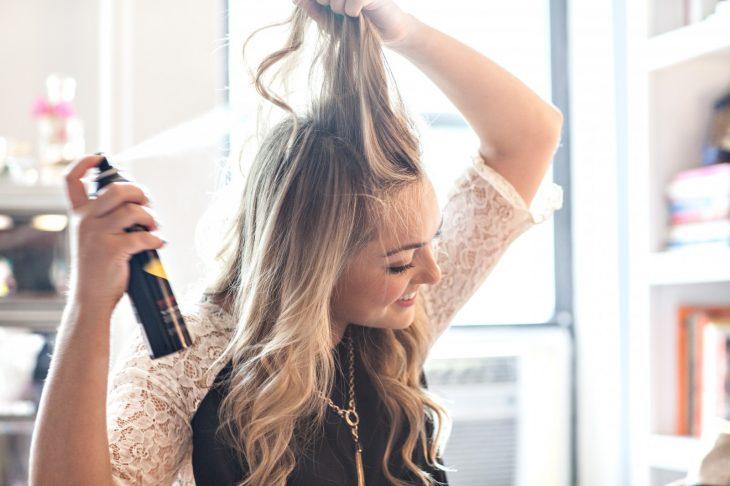 mujer cabello rubio aplicándose spray