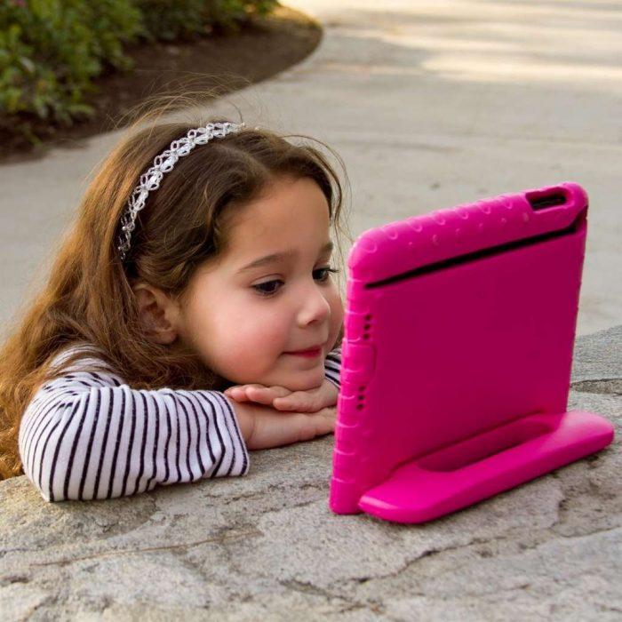 niña sentada viendo ipad rosa