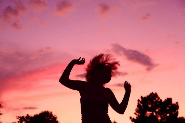 mujer saltando y cielo de atardecer rosa