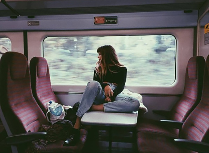 Joven sentada en la mesa central de un tren.