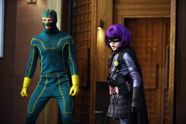 chico vestido de superheroe y chica peluca morada kiss ass