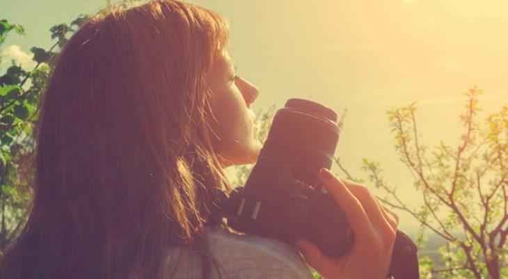 mujer con cámara fotográfica y arboles