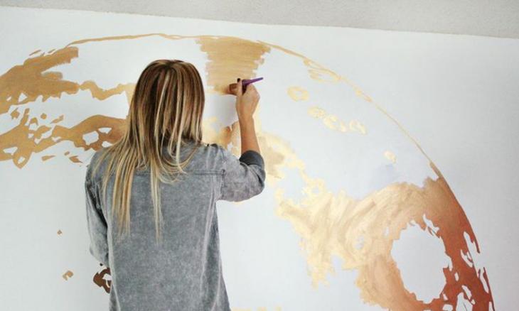 mujer rubia de espaldas pintando pared de color dorado