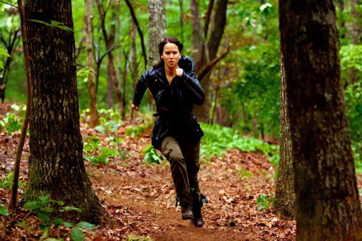mujer blanca y cabello negro corriendo en el bosque