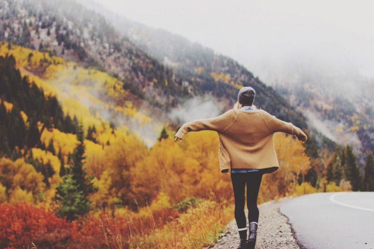 mujer abriendo sus brazos en paisaje de bosques y montañas