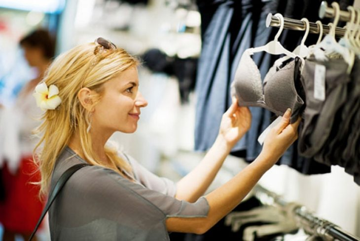mujer rubia mirando sostén en tienda