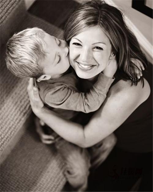 Niño besando a su mamá en la mejilla mientras ella lo abraza