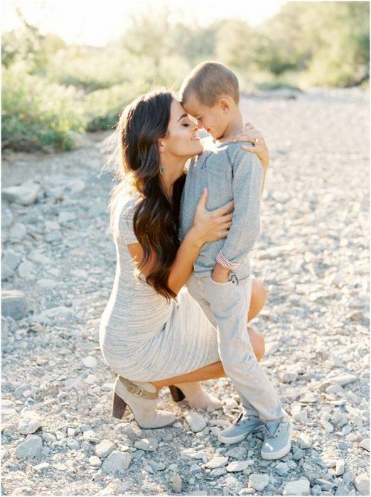 Chica hincada mirando a su hijo