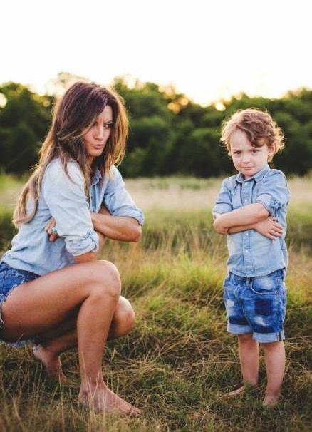 Mamá parada junto a su hijo mientras los dos cruzan los brazos