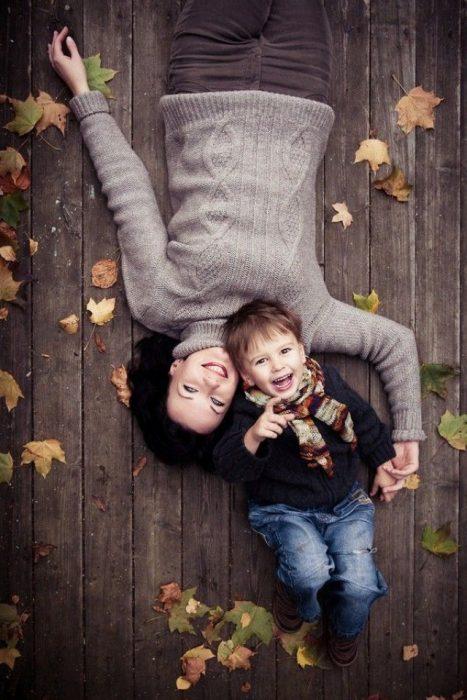 Mujer recostada en el suelo junto a su pequeño hijo