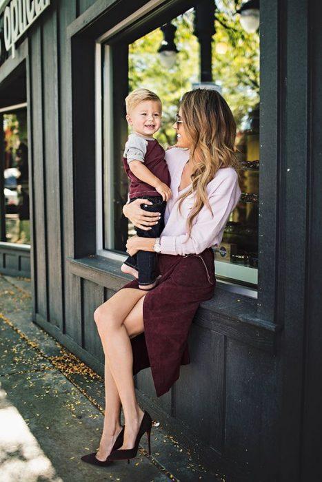 Mujer sentada en una ventana sosteniendo a su hijo