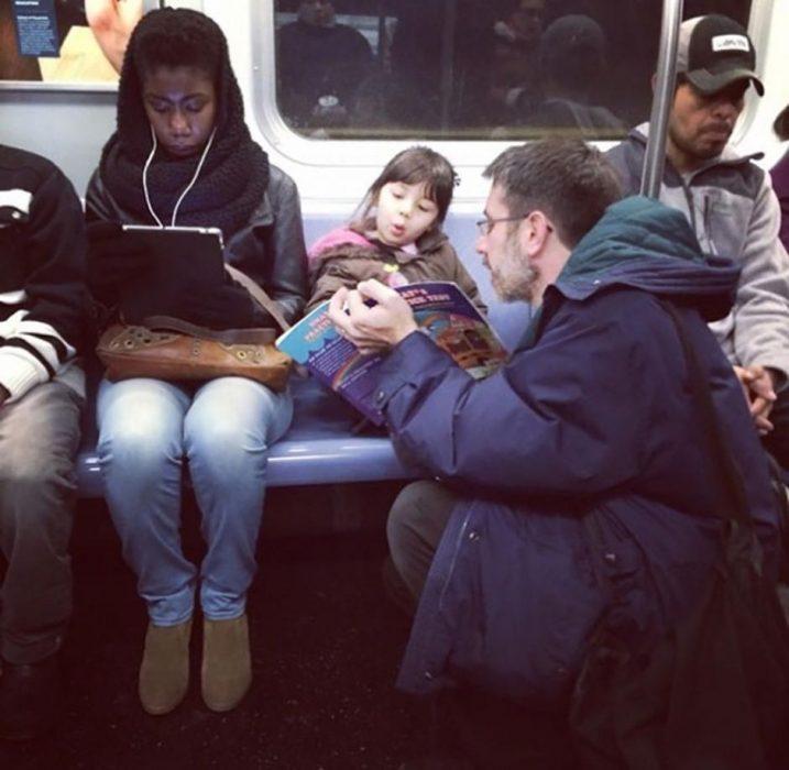 hombre sentado en el metro leyendole a una niña