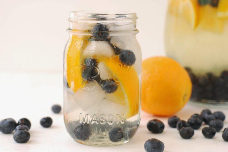 Agua de naranja y arándano con hielos servido en un vaso con agua