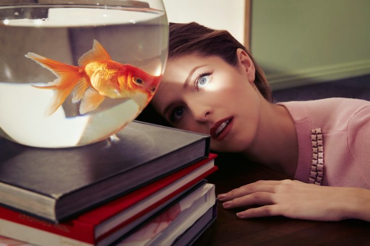 mujer peliroja mirando a un pez en pecera