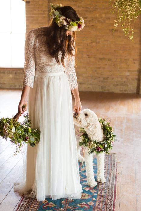 novia con vestido blanco y su perro con collar de flores