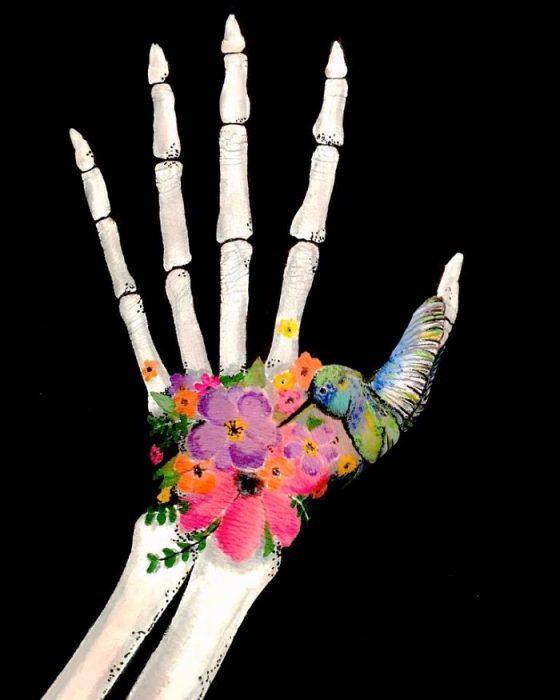 Chica que crea ilusiones ópticas en su mano con una calavera dibujada en su mano