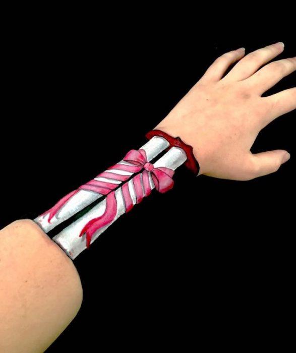 Chica que crea ilusiones ópticas en su mano, con huesos y un moño dibujados en ella