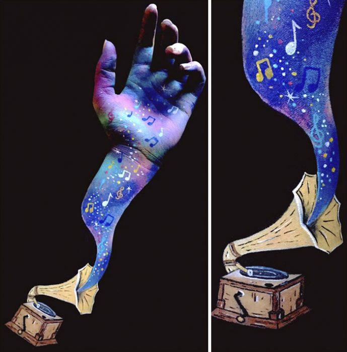 Chica que crea ilusiones ópticas en su mano, con una caja musical dibujada en su mano