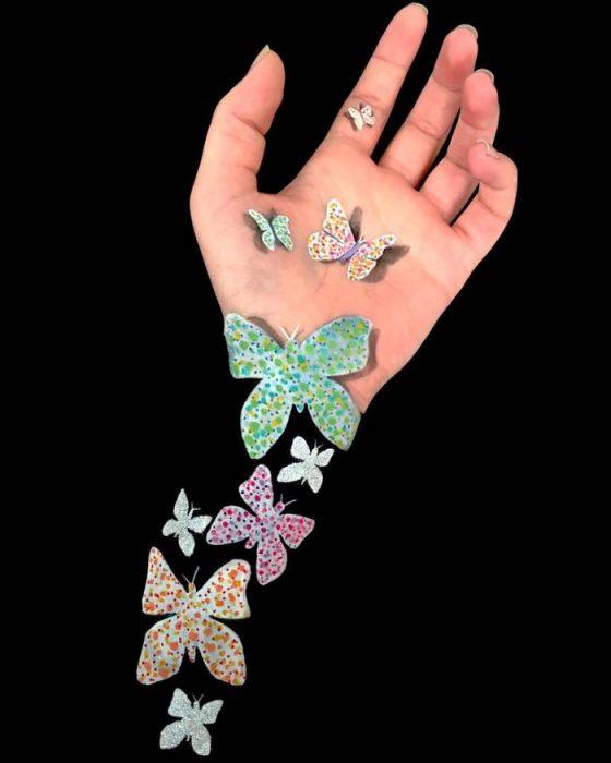 Chica que crea ilusiones ópticas en su mano con mariposas dibujadas en su brazo