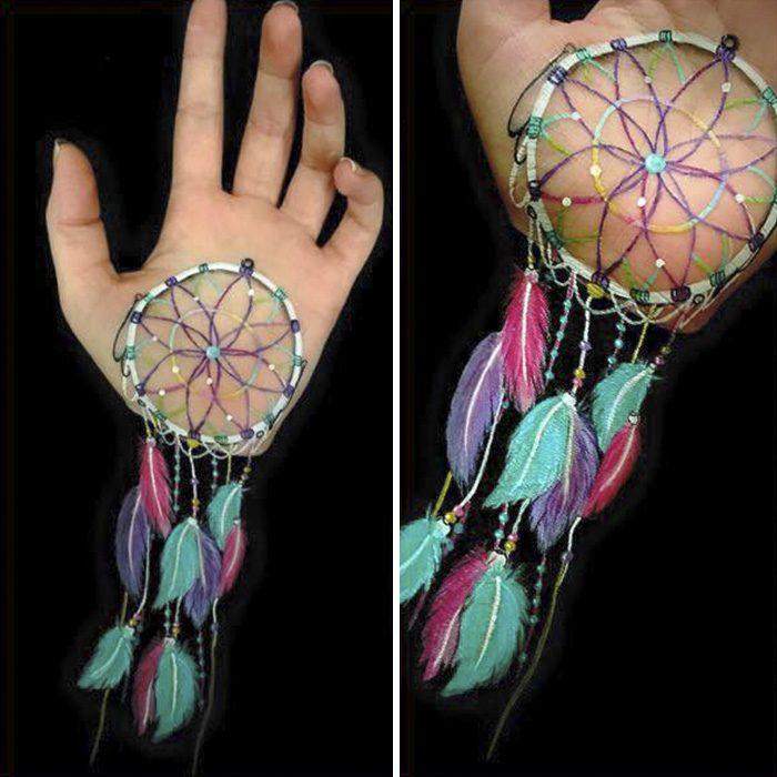 Chica que crea ilusiones ópticas en su mano, con un atrapa sueños dibujado en su brazo
