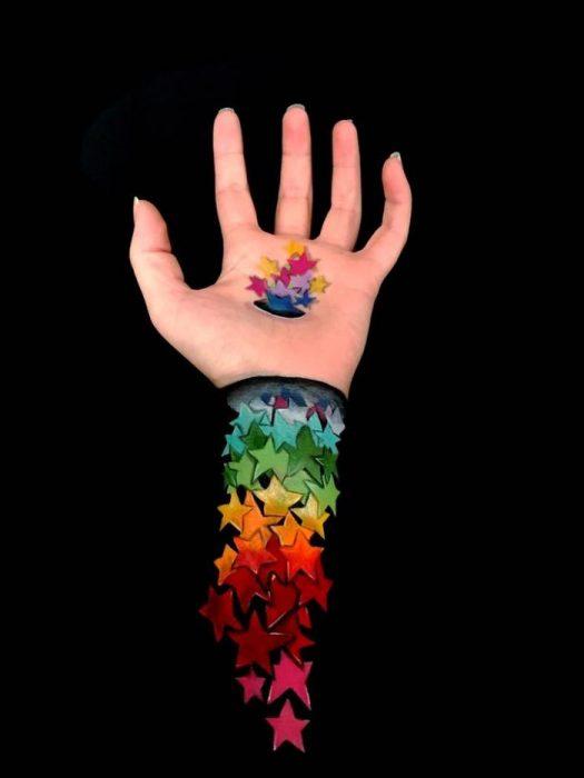 Chica que crea ilusiones ópticas en su mano, con estrellas dibujadas en su brazo