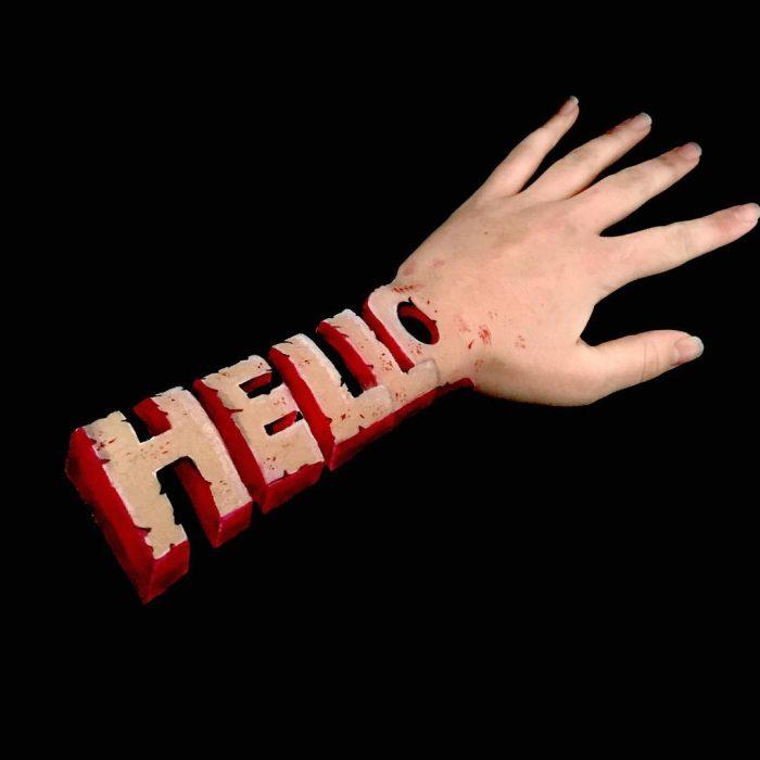 Chica que crea ilusiones ópticas en su mano, con la palabra hello dibujada sobre su brazo