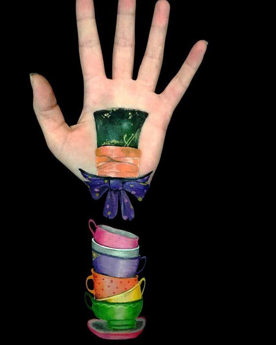 Chica que crea ilusiones ópticas en su mano, con el sombrero loco dibujado sobre su brazo