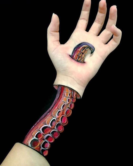 Chica que crea ilusiones ópticas en su mano, con un pulpo dibujado en ella