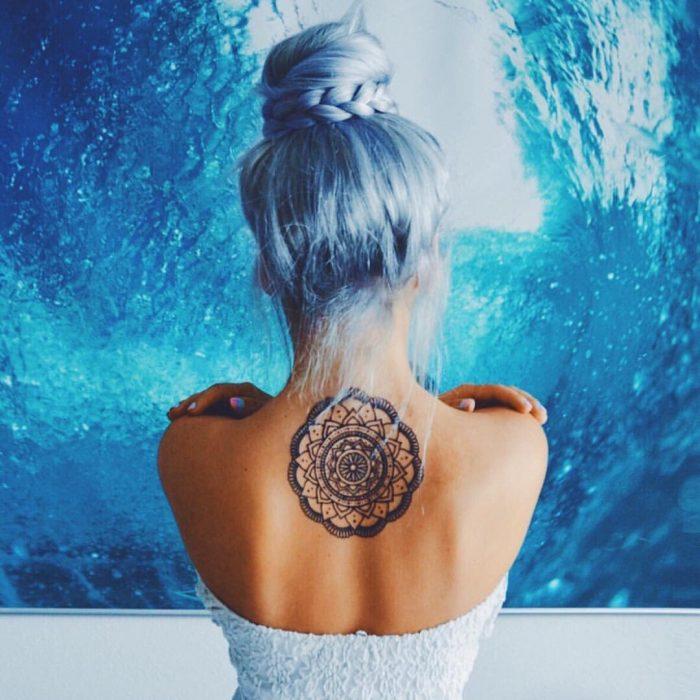Chica con cabello azul y tatuaje en la espalda