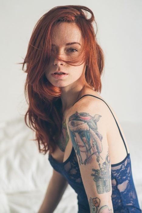 Chica peliroja con tatuajes en el brazo