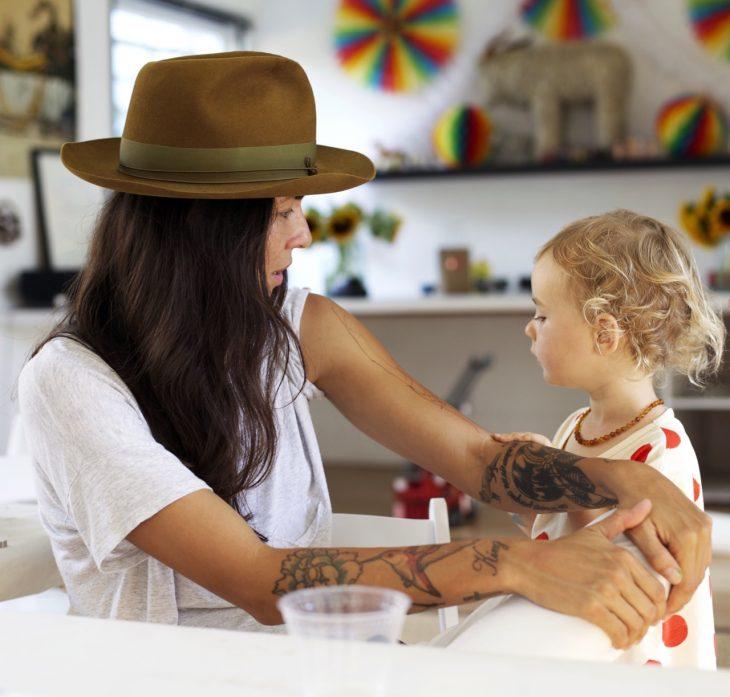 Chica con tatuajes cuidando un bebé