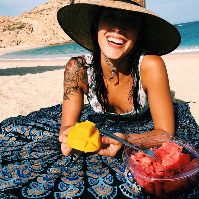 Chica con el hombro tatuado en la playa