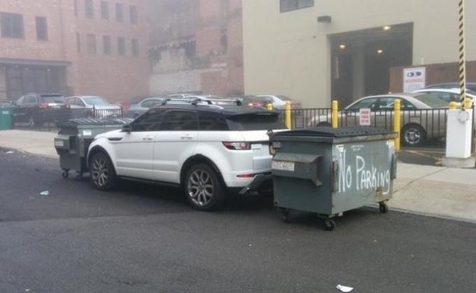 Contenedores de basura bloqueando el paso para una camioneta mal estacionada