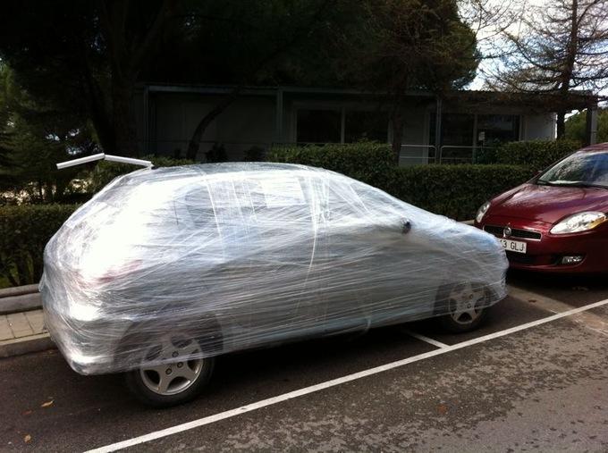 Automovil lleno de papel transparente porque está estacionado en un mal lugar
