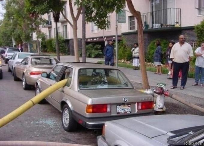 Carro con la manguera de los bomberos atravesada en la parte trasera por bloquear un hidrante
