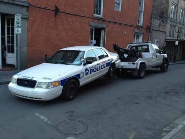 Grua llevandose a un policía por estar estacionado en un mal lugar