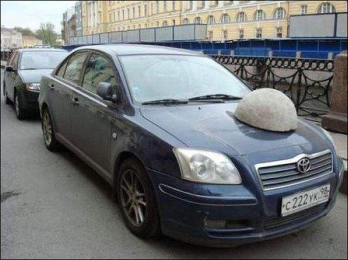 Piedra sobre el cofre de un carro que está estacionado en un lugar prohibido