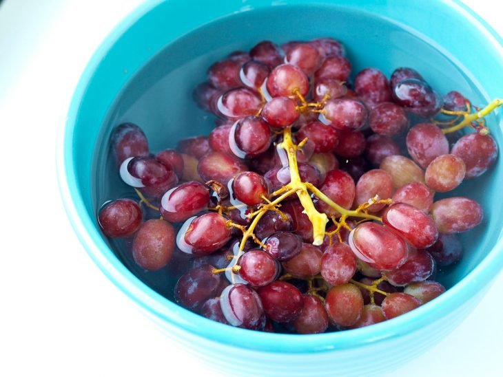 Uvas dentro de un recipiente con agua caliente para rehidratarlas