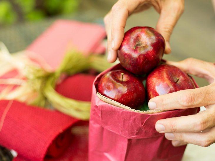 Manzanas rojas dentro de una bolsa de papel color rojo