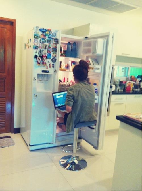 Chica estudiando frente al refrigerador