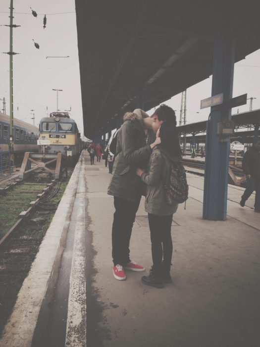 Pareja besándose en un anden de tren