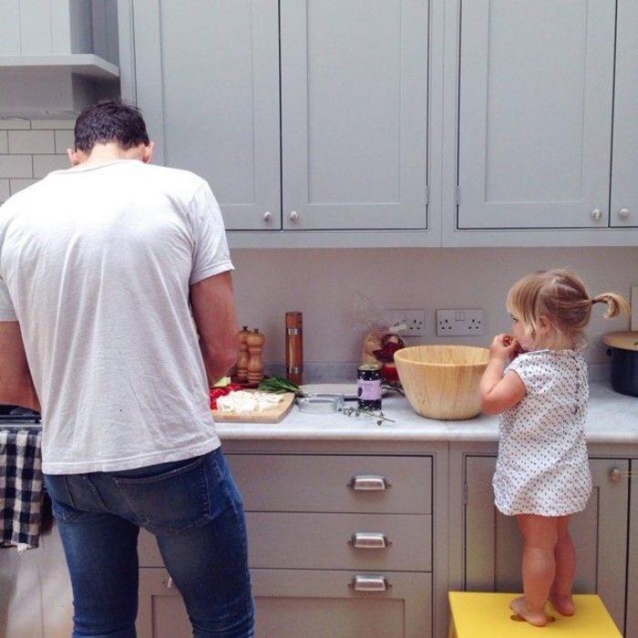 Niña cocinando junto a su papá en la cocina