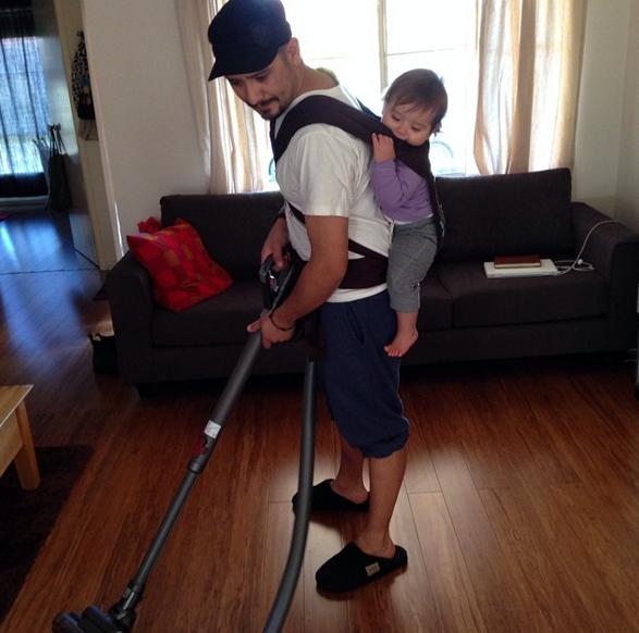 Hombre aspirando la sala de su casa mientras carga a su bebé