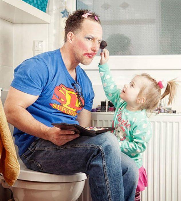 Papá sentado e la taza del baño viendo como su hija lo maquilla