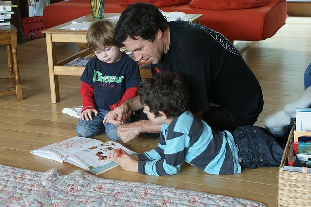 Papá sentado junto a sus hijos haciendo la tarea
