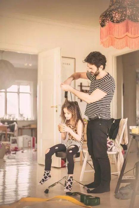 Hombre peinando a su hija con una pinza para bucles
